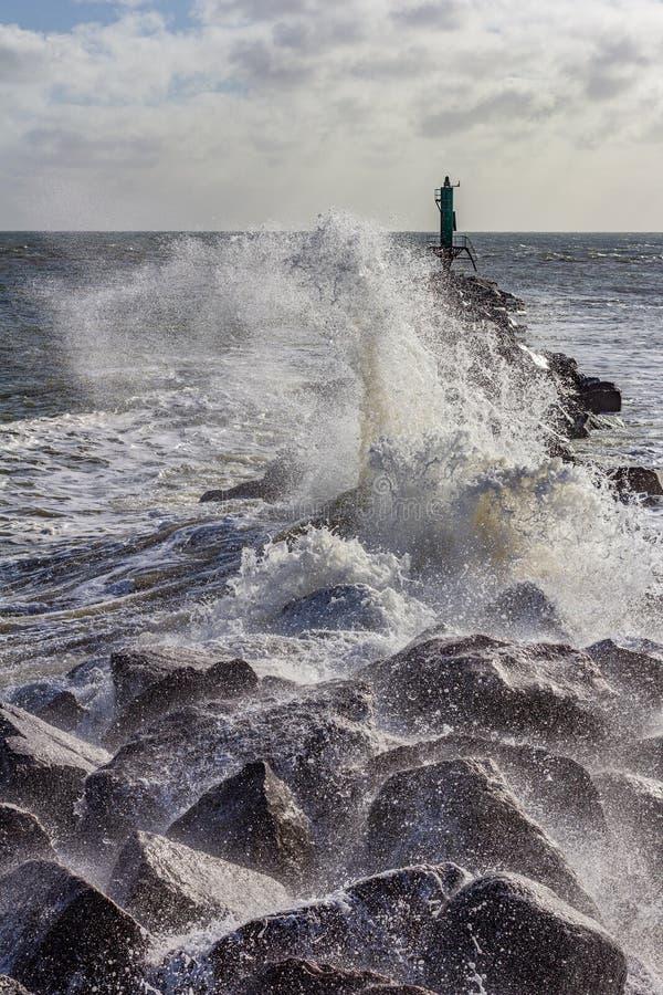 Onda que se estrella sobre un embarcadero Ramsgate, Inglaterra de la roca foto de archivo