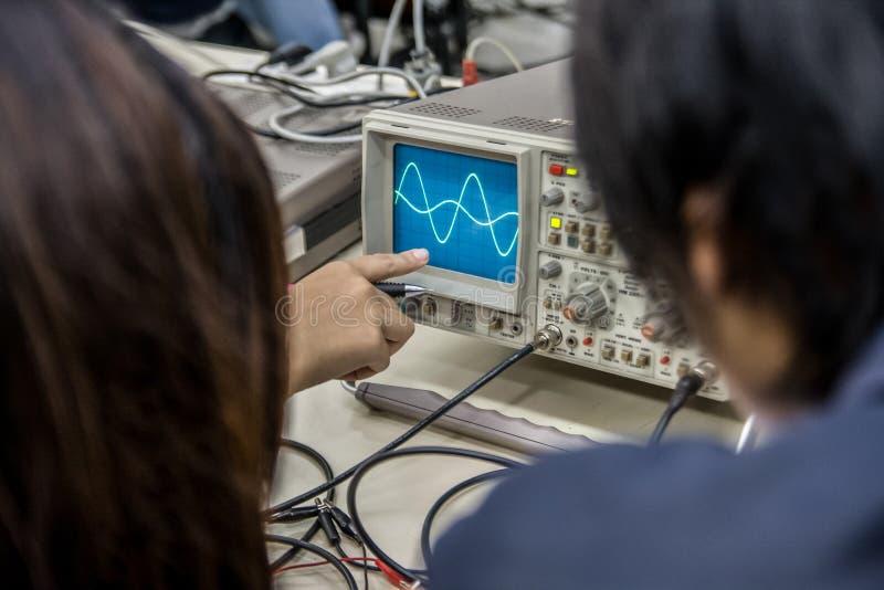 Onda sinusoidal del punto de los estudiantes en el osciloscopio imagenes de archivo