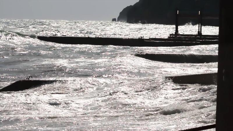 Onda y embarcadero del mar en la puesta del sol con los rayos del sol tiro Puesta del sol, tormenta en el mar, rompeolas Puesta d fotos de archivo libres de regalías