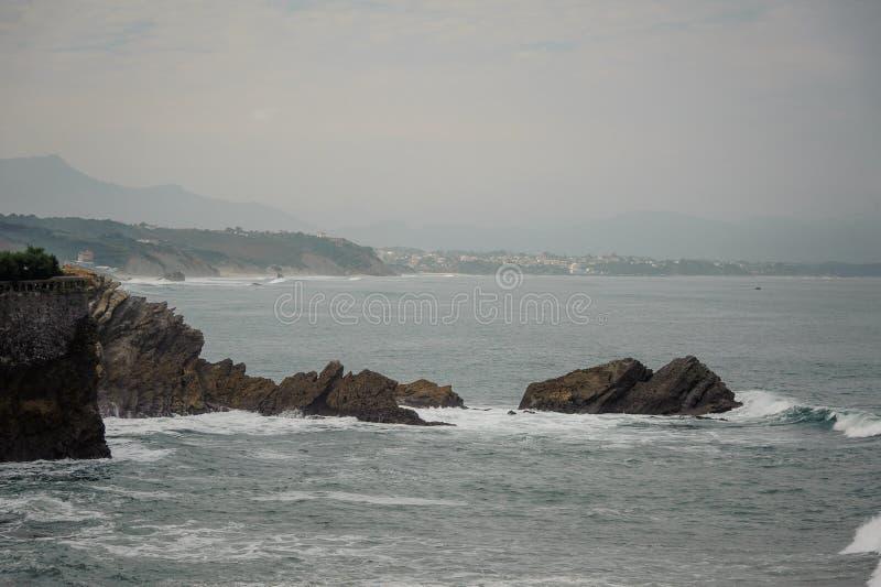 Ondas altas que batem a costa de mar perto do penhasco e das rochas foto de stock
