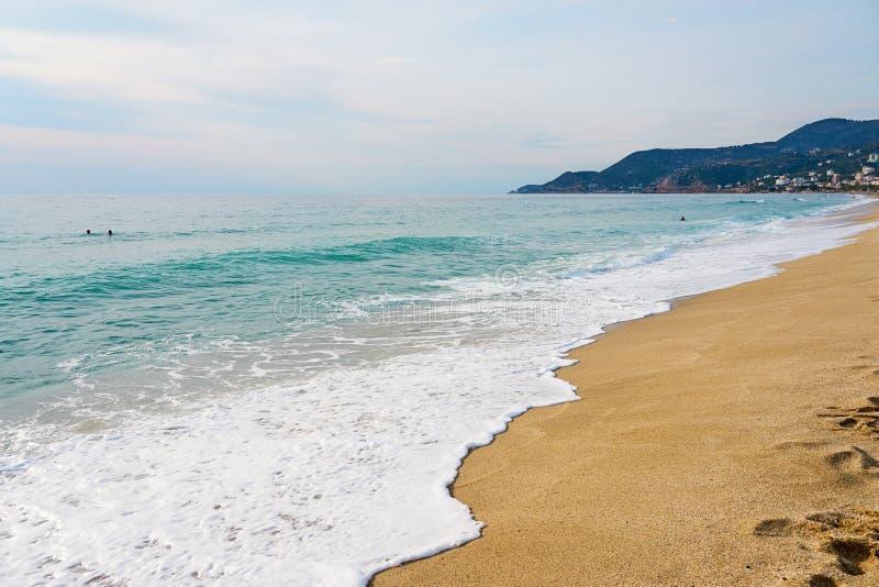 Ondas com a espuma que bate a areia na praia de Kleopatra em Alanya, Turquia fotos de stock royalty free
