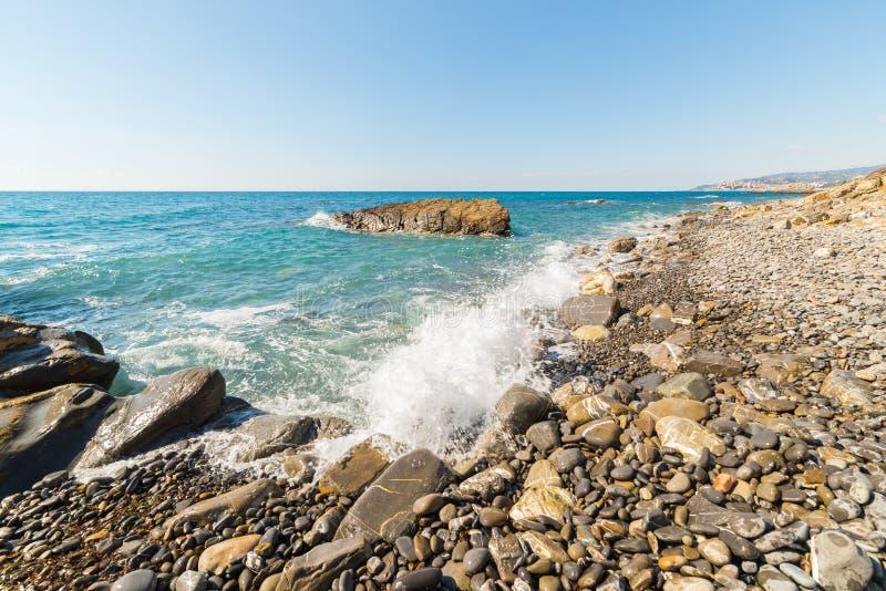 Ondas de agua que se rompen en las gravas, los guijarros y los cantos rodados de una playa vacía en la costa costa rocosa dura de foto de archivo