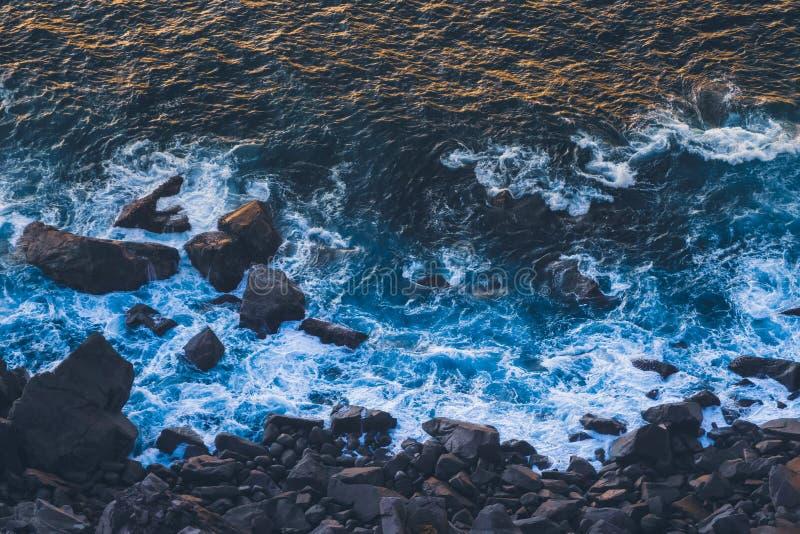 Ondas de fractura azules profundas de Océano Atlántico en orilla oscura del basalto en la puesta del sol fotografía de archivo libre de regalías