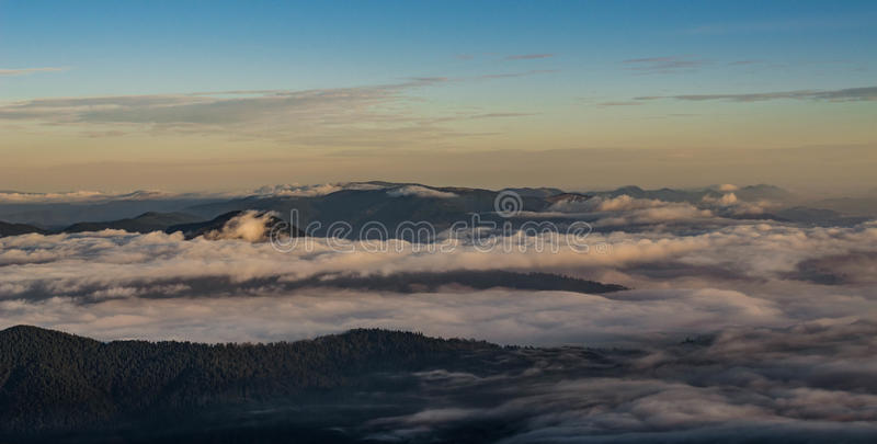 Ondas de las nubes que ruedan sobre las montañas fotos de archivo libres de regalías