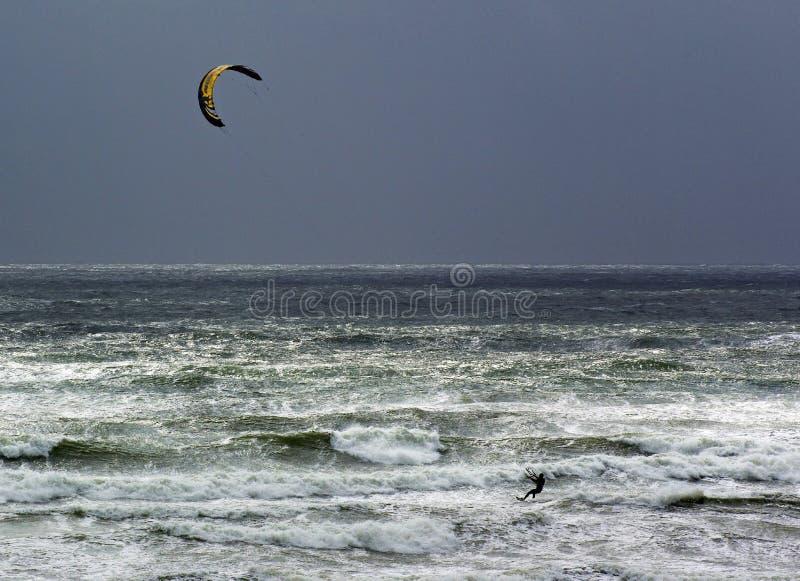 Ondas de océano del montar a caballo de la persona que practica surf de la cometa foto de archivo