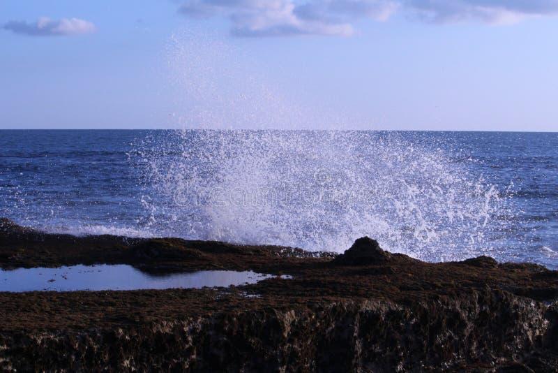 Ondas de oceano que batem a rocha da praia imagem de stock