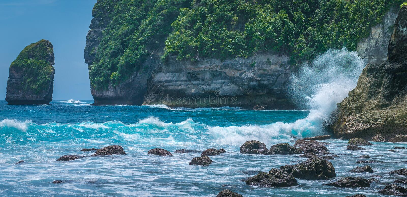 Ondas de oceano que hitiing rochas no litoral de Tembeling na ilha de Nusa Penida, Bali Indonésia imagem de stock royalty free