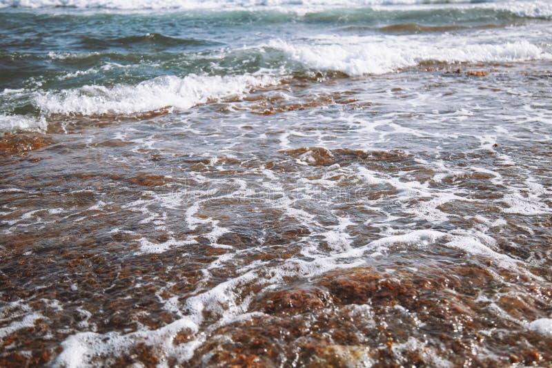 Ondas de piedra salvajes de la playa y del mar que se estrellan en la roca y que hacen una malla del agua con la burbuja fotografía de archivo libre de regalías