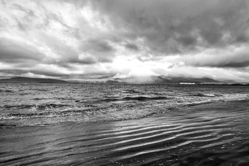 Ondas do mar no Sandy Beach em reykjavik, Islândia Seascape com água cinzenta no céu nebuloso Poder da natureza Desejo por viajar fotos de stock
