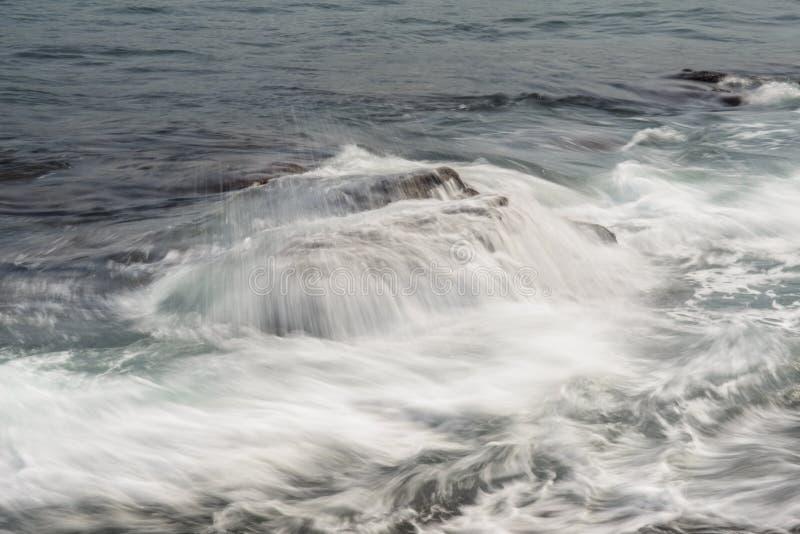 Ondas do mar que batem as rochas da costa imagens de stock