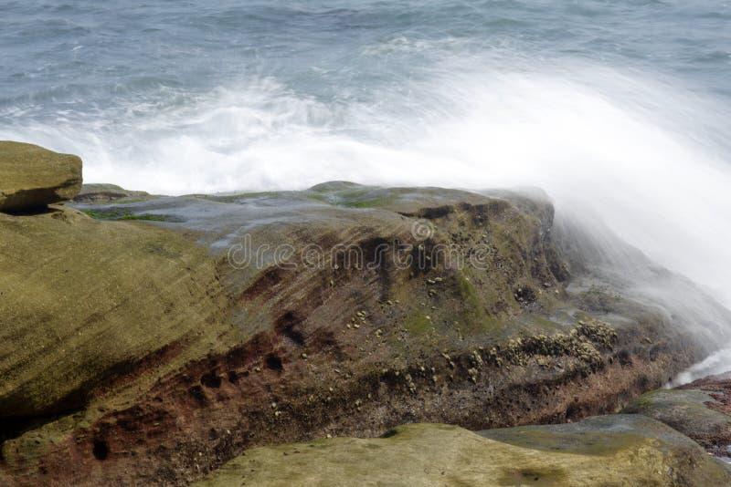 Ondas do mar que batem as rochas da costa imagem de stock