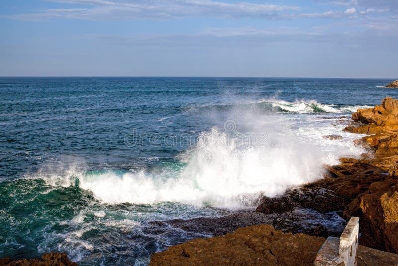 Ondas do mar que deixam de funcionar contra as rochas imagens de stock