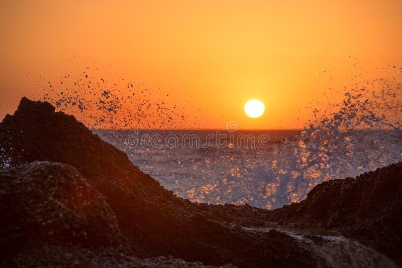 Ondas do mar que esmagam e que espirram nas rochas em uma praia tropical, na luz morna bonita do por do sol fotos de stock royalty free