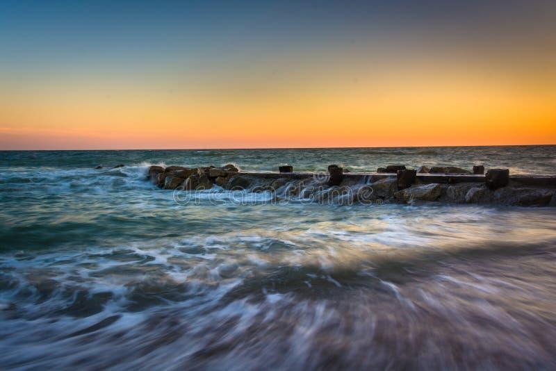 Ondas e um molhe no por do sol no Oceano Atlântico em Edisto Beac imagem de stock royalty free