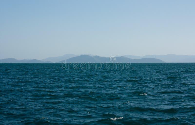 Ondas, el mar y algunas islas en la distancia en los Pentecostés en Australia imagen de archivo