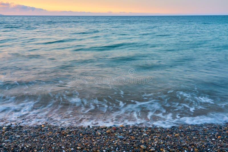 Ondas em um Pebble Beach em um por do sol imagem de stock