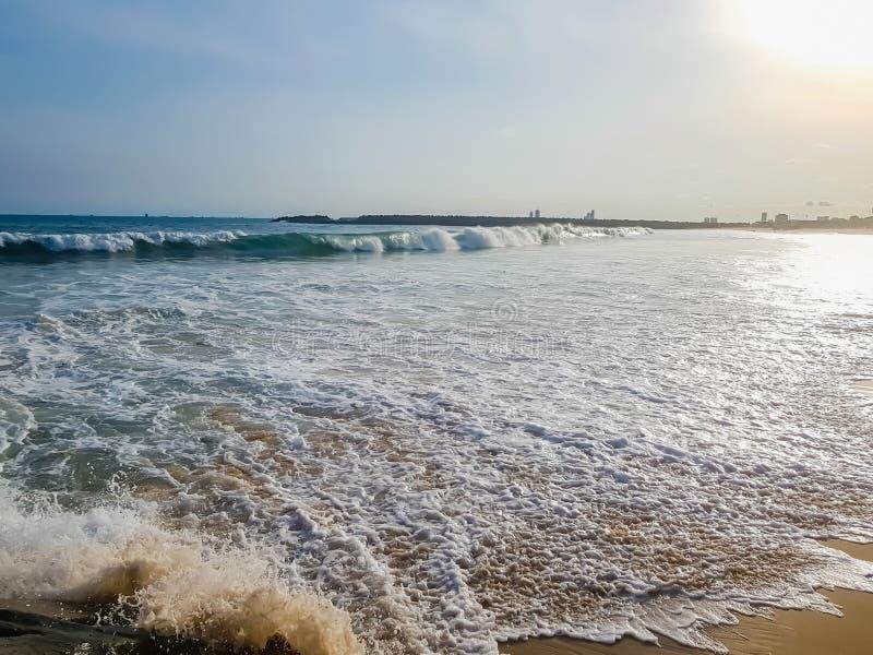Ondas em uma praia com o sol que brilha brilhantemente no c?u, refletindo na ?gua Mar e c?u azuis Espuma branca da ressaca do oce foto de stock royalty free