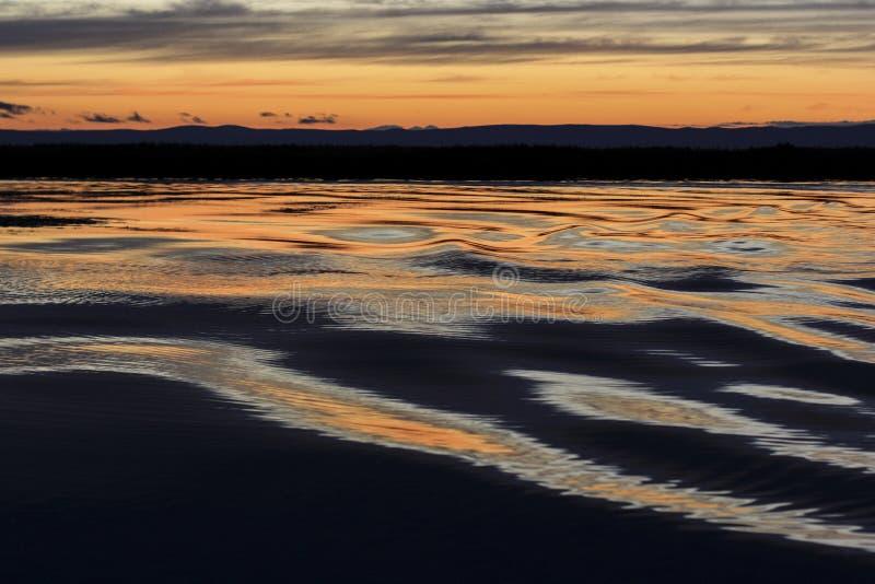 Ondas en el lago en la puesta del sol imagen de archivo