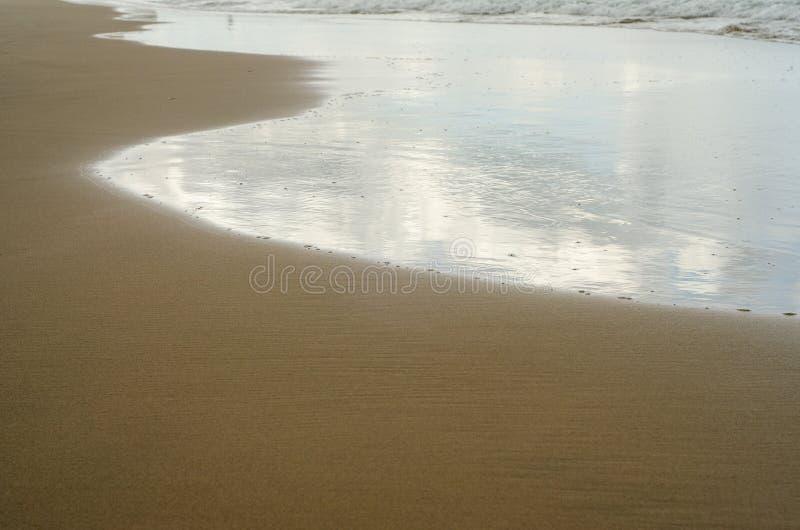Ondas en la orilla con reflexiones de nubes fotografía de archivo