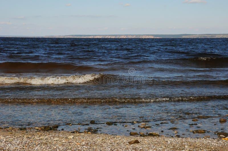 Ondas en la orilla en una playa abandonada Bahía del río o del mar, horizonte foto de archivo