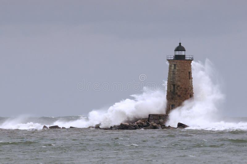 Ondas enormes que deixam de funcionar em torno da torre de pedra do farol em Maine fotos de stock royalty free