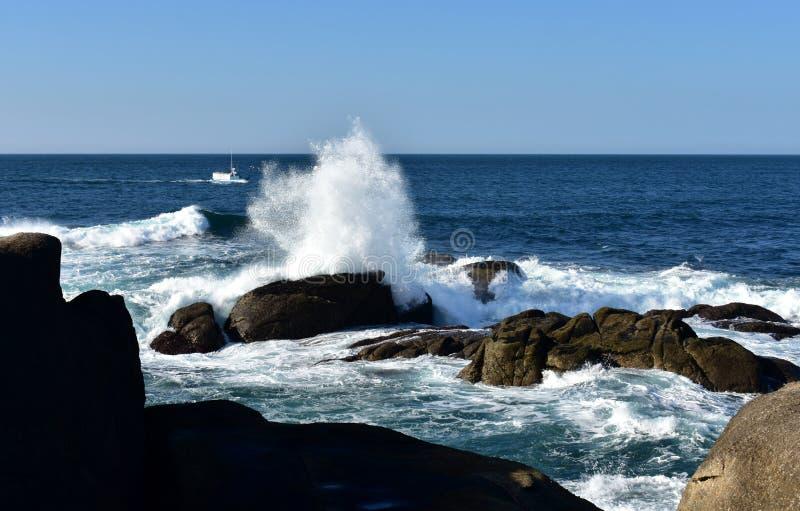 Ondas grandes que salpican contra las rocas y el barco de pesca Mar azul con la espuma blanca, día soleado Galicia, España fotos de archivo libres de regalías