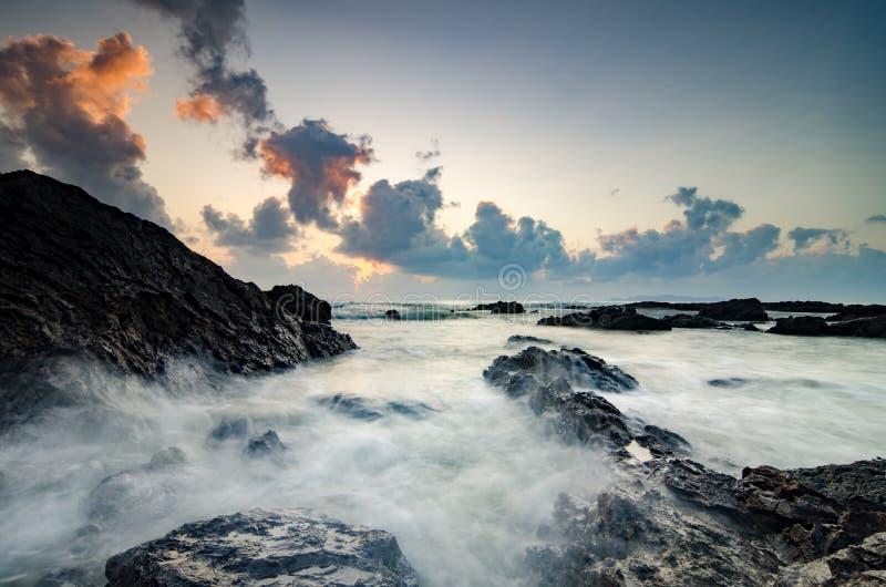 Ondas hermosas que salpican en la formación de rocas única sobre fondo de la salida del sol imagen de archivo