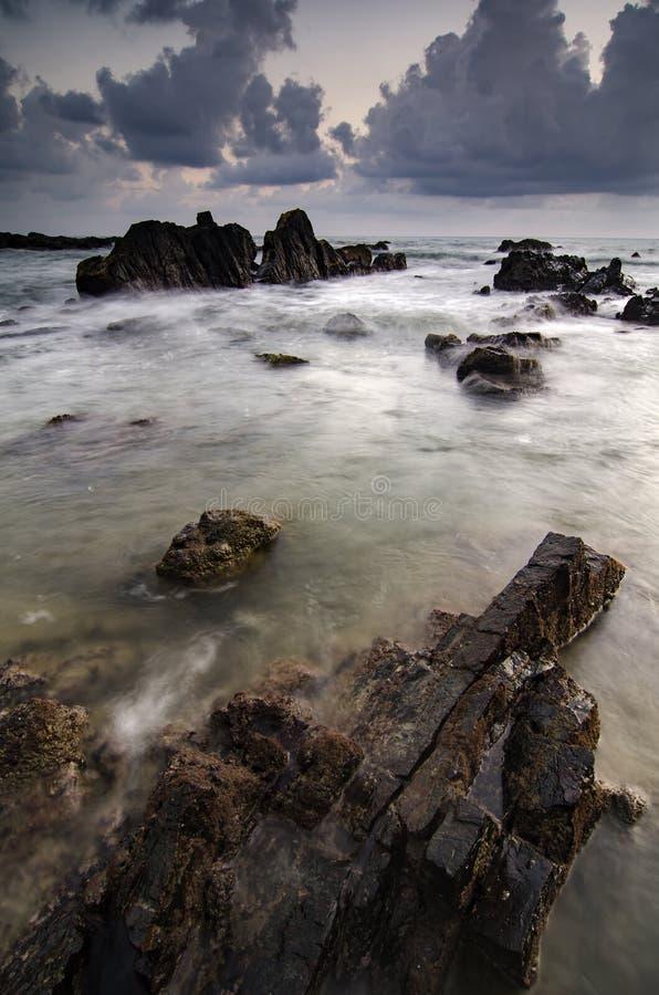 Ondas hermosas que salpican en la formación de rocas única sobre fondo de la salida del sol imagenes de archivo