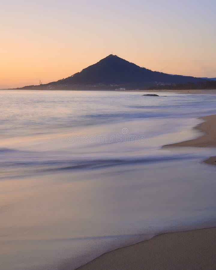 Ondas lisas sobre una playa arenosa en la puesta del sol con la montaña en fondo imagen de archivo libre de regalías