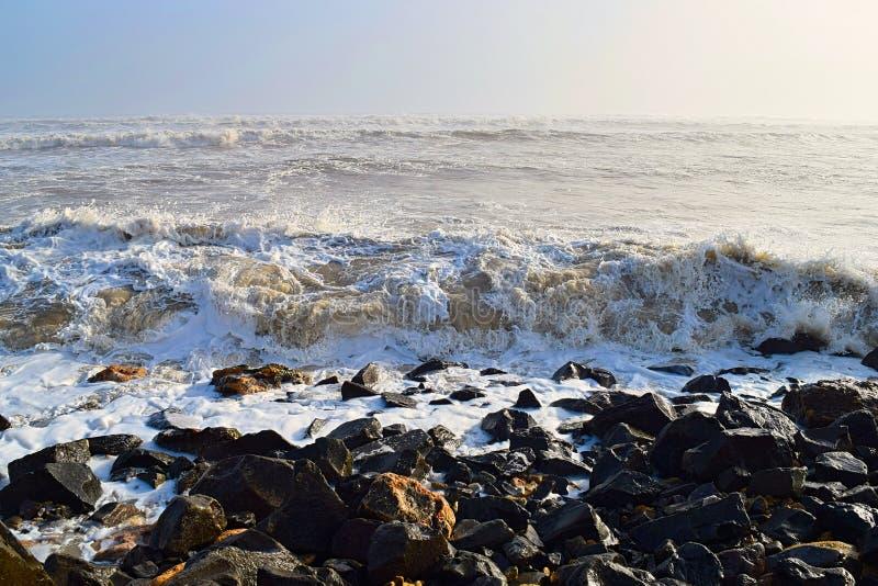 Ondas marítimas durante o alto curso na costa rochosa no dia ensolarado com oceano infinito - Fundo natural das paisagens marítim imagens de stock royalty free