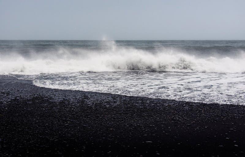 Ondas na praia preta de Reynisfjara da areia em Islândia imagens de stock