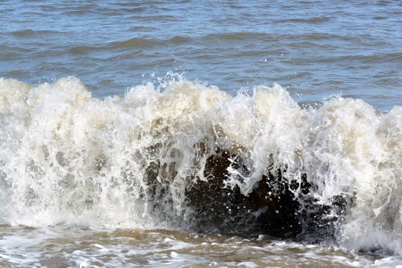 Ondas pequenas que deixam de funcionar na costa perto de Bridlington imagem de stock