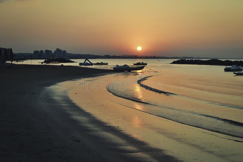 Ondas perezosas en la puesta del sol imagen de archivo