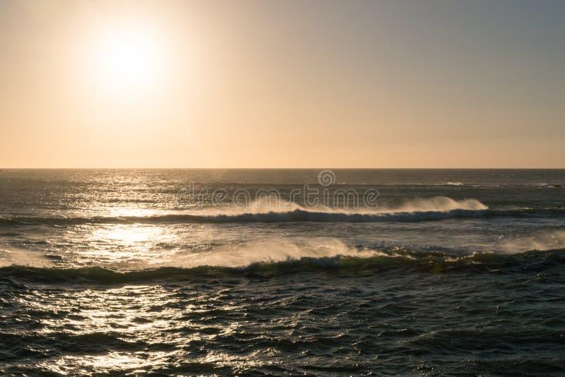 Ondas pitorescas do mar perto da costa rochosa de Oceano Atlântico no tempo do por do sol foto de stock royalty free