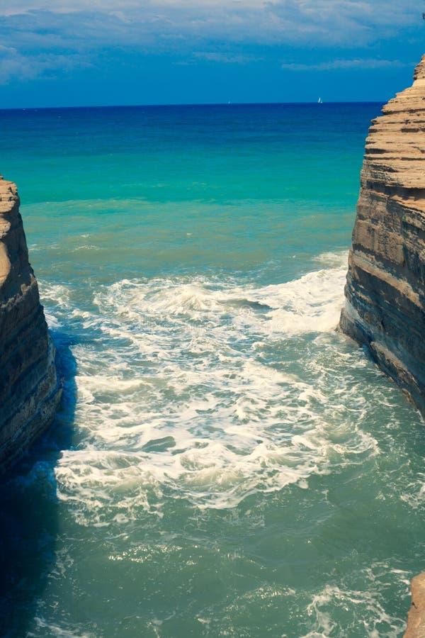 Ondas que causan un crash en rocas Againts del movimiento del océano las piedras Mar azul que arruina una montaña Grava sensacion imagen de archivo libre de regalías