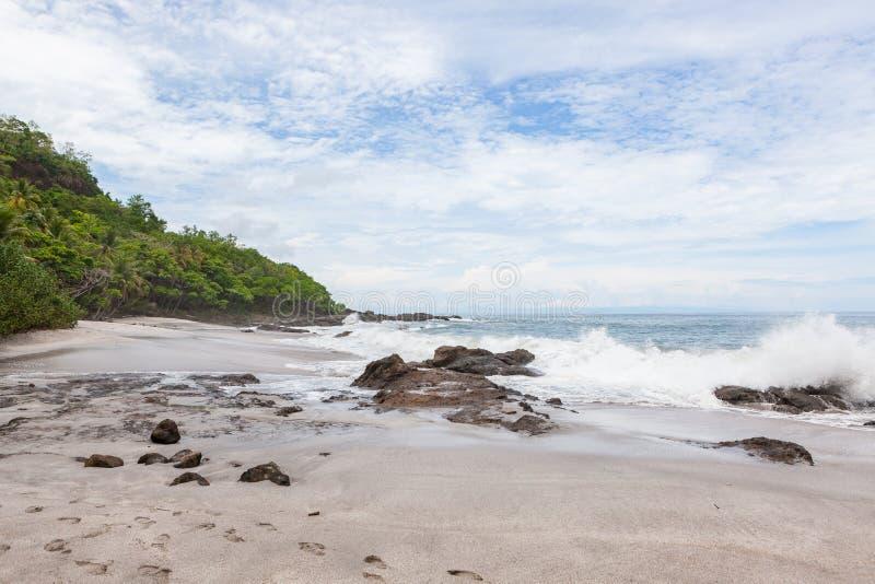 Ondas que deixam de funcionar à praia do montezuma das rochas fotos de stock