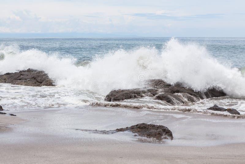 Ondas que deixam de funcionar à praia do montezuma das rochas imagens de stock
