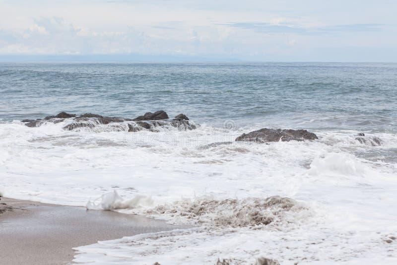Ondas que deixam de funcionar à praia do montezuma das rochas imagem de stock
