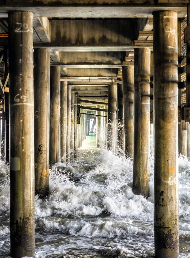 Ondas que deixam de funcionar as colunas sob Santa Monica Pier - Santa Monica, Los Angeles, LA, Califórnia, CA fotografia de stock royalty free