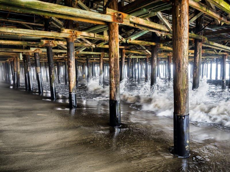 Ondas que deixam de funcionar as colunas sob Santa Monica Pier - Santa Monica, Los Angeles, LA, Califórnia, CA imagens de stock royalty free