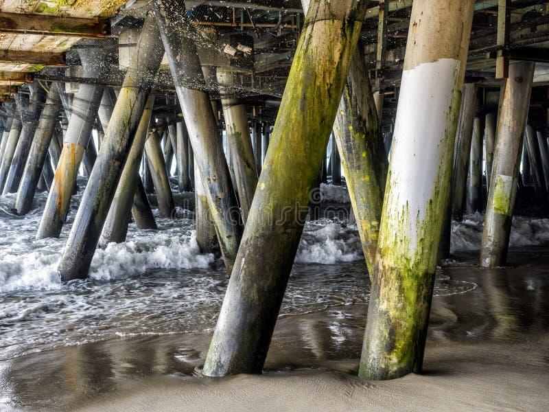 Ondas que deixam de funcionar as colunas sob Santa Monica Pier - Santa Monica, Los Angeles, LA, Califórnia, CA fotografia de stock