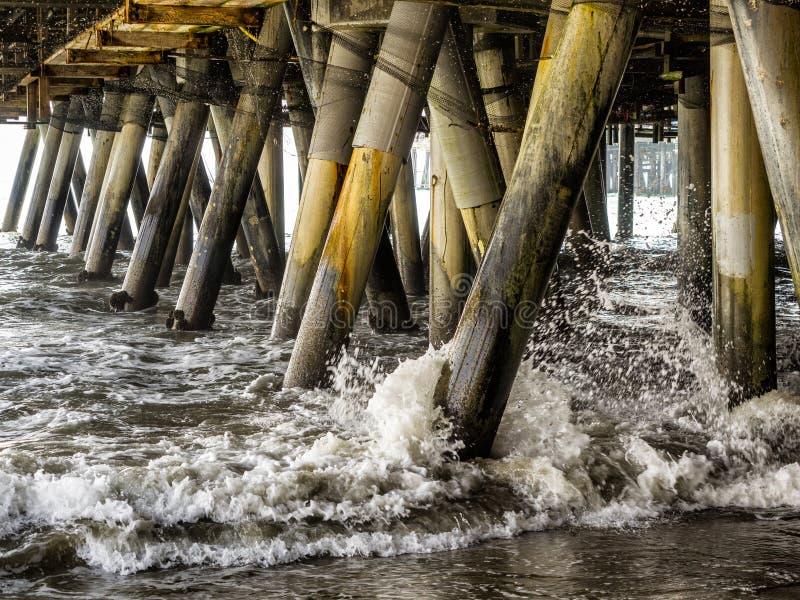 Ondas que deixam de funcionar as colunas sob Santa Monica Pier - Santa Monica, Los Angeles, LA, Califórnia, CA fotos de stock