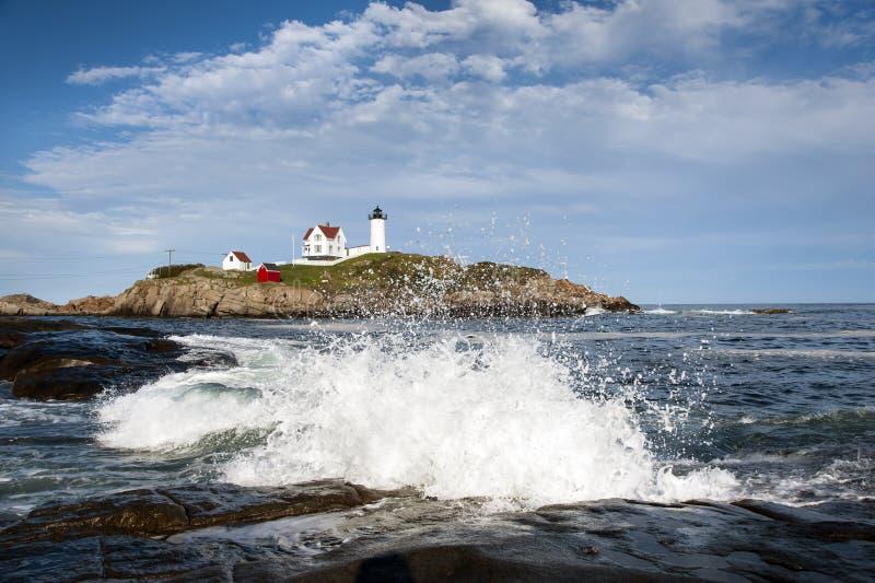 Ondas que deixam de funcionar em rochas pelo farol em Maine foto de stock