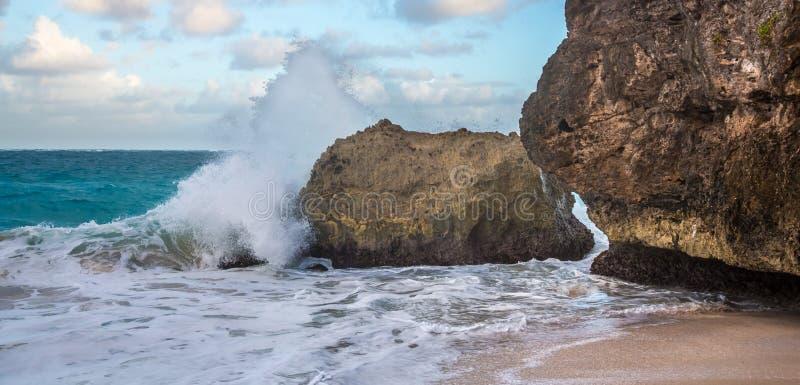 Ondas que deixam de funcionar sobre rochas na costa tropical fotografia de stock