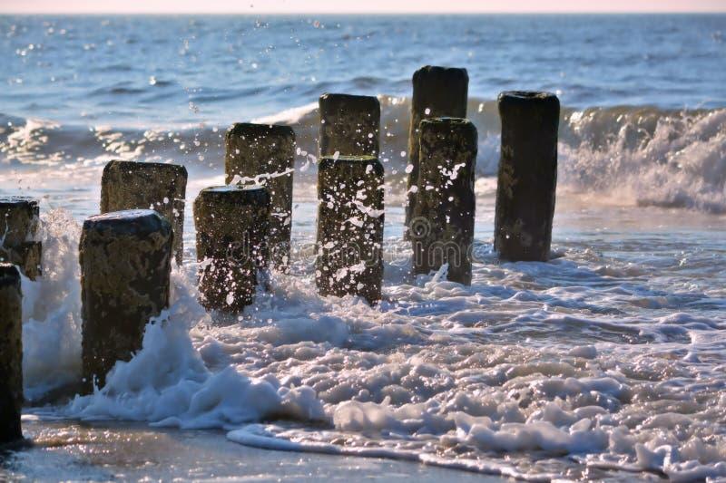 Ondas que espirram acima contra o molhe de madeira no oceano fotos de stock