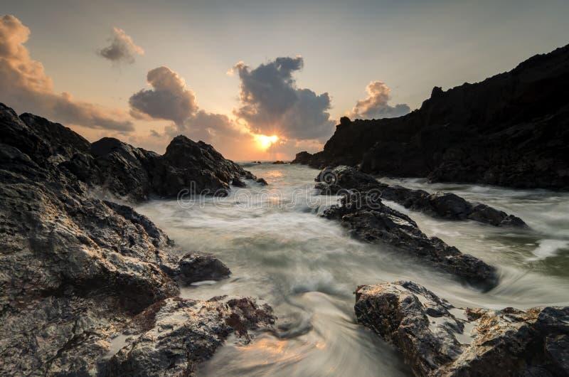 Ondas que espirram na formação de rochas original sobre o fundo impressionante do nascer do sol imagem de stock