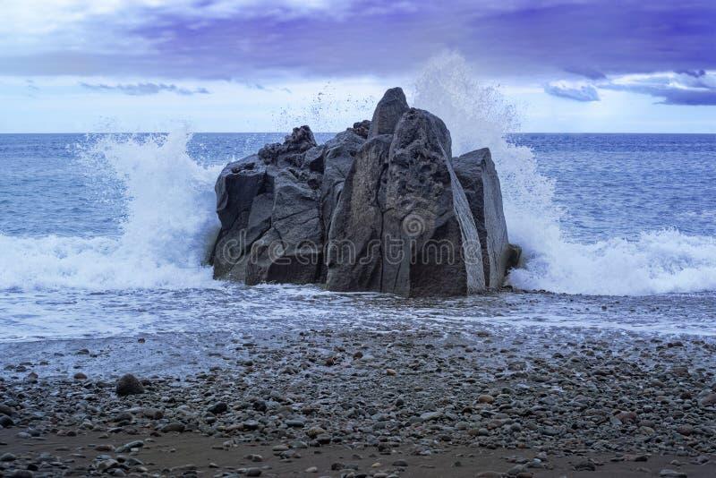 Ondas que espirram na rocha no por do sol fotografia de stock