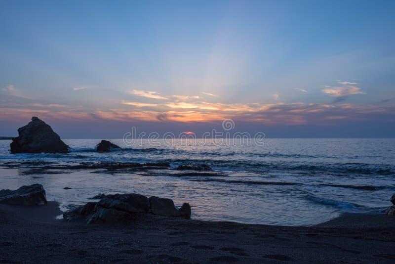 Ondas que espirram perto da rocha solitária, por do sol imagem de stock