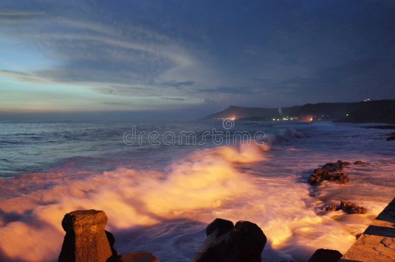 Ondas que golpean la orilla en la oscuridad fotografía de archivo