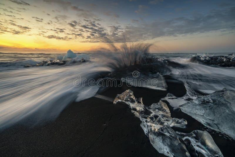 Ondas que rabian que rompen bloques de hielo en la salida del sol en Diamond Beach foto de archivo